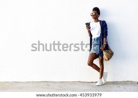 Full length portrait of urban woman standing against while wall and listening to music on her smart phone