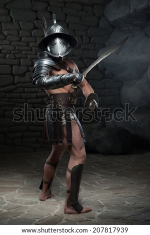 Full length portrait of warrior gladiator with muscular body in helmet holding sword, sideview on dark background. Concept of masculine power, strength - stock photo