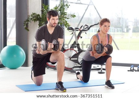 Full length portrait of woman and man lifting barbells during a gym workout at fitness center.