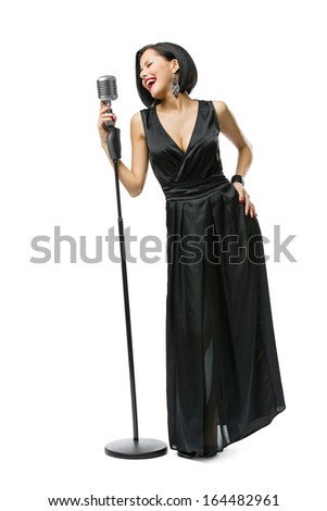 Full-length portrait of woman musician wearing long black evening dress and holding mic - stock photo