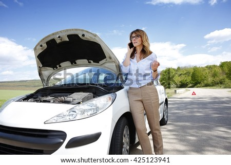 Full length portrait of woman standing her breaking down car and calling roadside assistance.