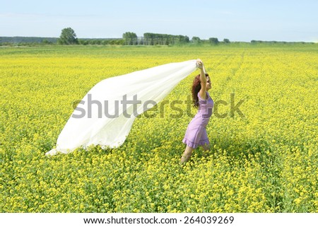Full length portrait of woman walk in yellow grass meadow Raps field with a white transparent tissue scarf cloth texture Idea symbol concept free light Freedom life Empty space for inscription  - stock photo