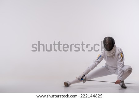 Full-length portrait of woman wearing white fencing costume and black fencing mask sitting like ninja looking at us. Isolated on white background - stock photo