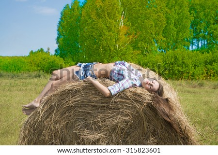 Full length portrait of young adult Cowgirl lie on haystack against blue sky with clouds and summer field with hay Alone woman wear black hat , jeans shorts and stripped shirt  - stock photo