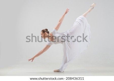 Full length portrait of young and beautiful modern style ballet dancer taking classical ballet poses, lifting leg up isolated on white background, studio shot - stock photo