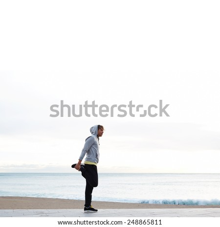 Full length portrait of young athletic man doing stretches next to the beach, young jogger stretching in the morning on seaside - stock photo