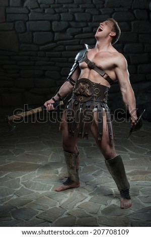 Full length portrait of young attractive warrior gladiator with muscular body holding shield and axe, screaming on dark background. Concept of masculine power, strength - stock photo