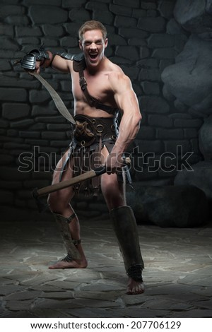 Full length portrait of young attractive warrior gladiator with muscular body posing with two swords, screaming on dark background. Concept of masculine power, strength - stock photo