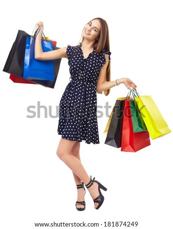 Full length portrait of young beautiful smiling happy woman holding many colorful shopping bags isolated on white background