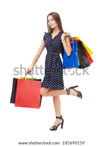 Full length portrait of young beautiful smiling woman holding many colorful shopping bags,standing on one leg, isolated on white background