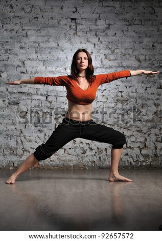 Full-length portrait of young beautiful woman doing yoga excercise against a brick wall