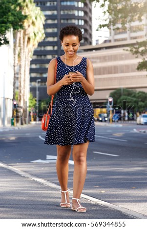 Full length portrait of young black woman walking in city with smart phone and purse
