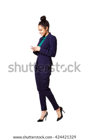 Full length portrait of young business woman using cell phone over white background - stock photo