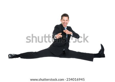 Full length portrait of young businessman doing splits while gesturing over white background - stock photo