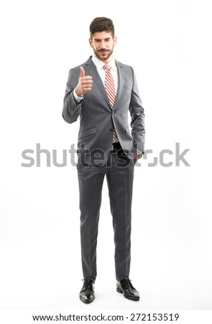 Full length portrait of young businessman standing against white background while looking at camera and showing thumb up. - stock photo