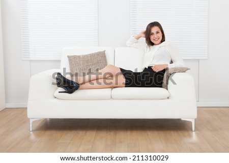 Full length portrait of young businesswoman sitting on sofa at home - stock photo