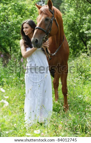 Full-length portrait of young charming brunette woman wearing white dress standing with brown horse and looking somewhere at summer green park. - stock photo