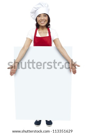 Full length portrait of young chef presenting billboard in front of camera - stock photo