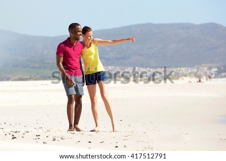 Full length portrait of young couple standing on the beach and looking at the sea - stock photo