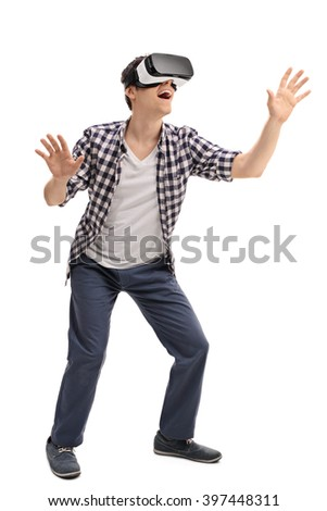 Full length portrait of  young excited man experiencing virtual reality isolated on white background - stock photo