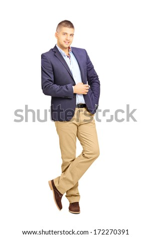 Full length portrait of young fashionable man leaning against a wall isolated on white background