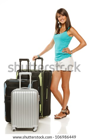 Full length portrait of young female standing with three suitcases going on holidays isolated on white background