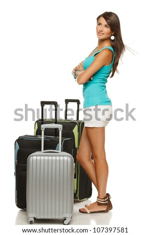 Full length portrait of young female standing with three suitcases going on holidays, looking to the side, isolated on white background