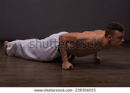 Full-length portrait of young handsome fair-haired bare-chested karate enthusiast stretching. Isolated on the dark background - stock photo
