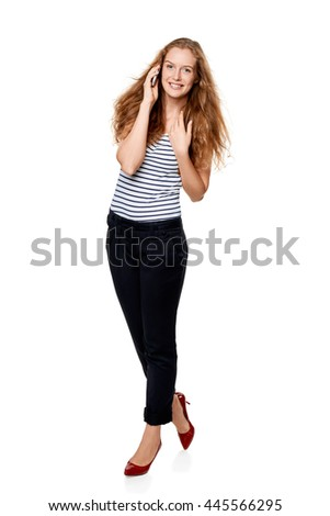 Full length portrait of young, happy beautiful woman talking on cell phone looking at the camera, over white background - stock photo