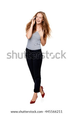 Full length portrait of young, happy beautiful woman talking on cell phone looking to the side at blank copy space, over white background - stock photo