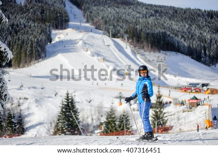 Full length portrait of young happy woman skier against ski slopes and ski-lift on background. Woman is wearing helmet skiing glasses gloves and blue ski suit. Winter sports concept. - stock photo