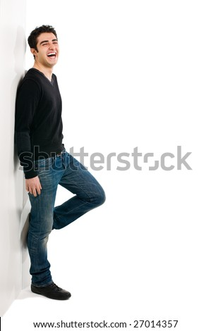 Full length portrait of young laughing man standing against white wall with copy space for your text - stock photo
