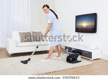 Full length portrait of young maid cleaning carpet with vacuum cleaner at home - stock photo