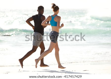 Full length portrait of young man and woman in sportswear running along the beach - stock photo