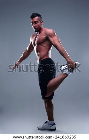 Full length portrait of young man athlete doing stretches exercises  - stock photo