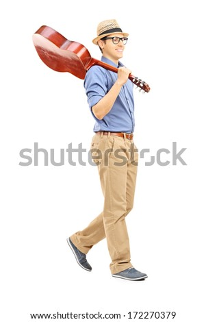 Full length portrait of young man holding an acoustic guitar over his shoulder isolated on white background - stock photo
