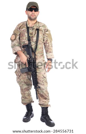 Full length portrait of young man in army clothes holding an automatic weapon against white background - stock photo