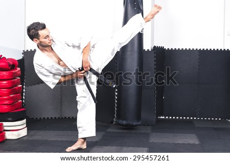Full length portrait of young man in kimono training ashihara martial art at the gym