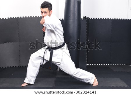 Full length portrait of young man in kimono training ashihara martial art at the gym - stock photo
