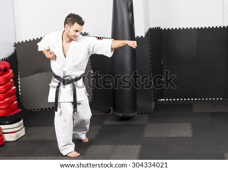 Full length portrait of young man in kimono training ashihara martial art in the gym - stock photo