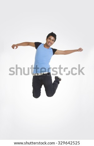 Full length portrait of young man jumping with arms outstretched over white background - stock photo