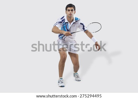 Full length portrait of young man playing badminton isolated over white background - stock photo