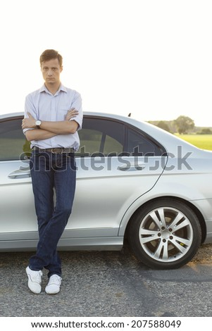 Full length portrait of young man standing by car at countryside - stock photo