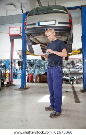 Full length portrait of young mechanic using laptop in his auto repair shop - stock photo