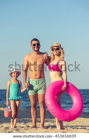 Full length portrait of young parents and their little daughter in swimsuits and sun glasses holding staff, looking at camera and smiling, standing on the sunny beach - stock photo