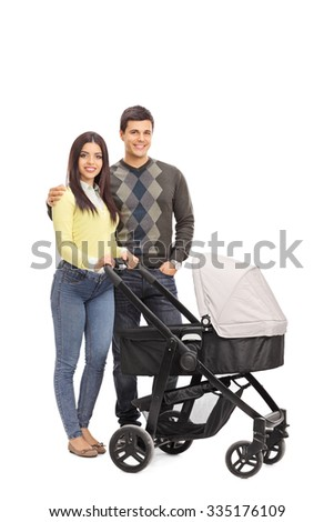 Full length portrait of young parents posing with a baby stroller and hugging isolated on white background