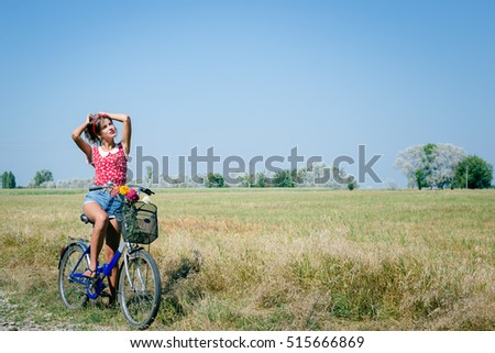 Full length portrait of young pinup woman cycling in fields under bright blue summer sky copy space image