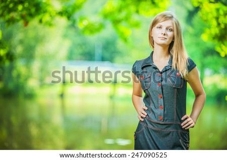 Full-length portrait of young pretty woman standing at summer green park. - stock photo