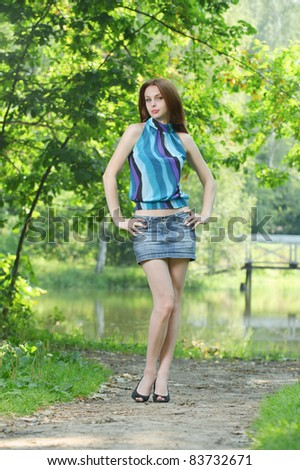 Full-length portrait of young pretty woman wearing blue blouse, jean skirt and black shoes standing at summer green park.