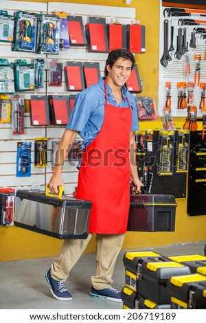 Full length portrait of young salesman carrying toolboxes while walking in hardware store